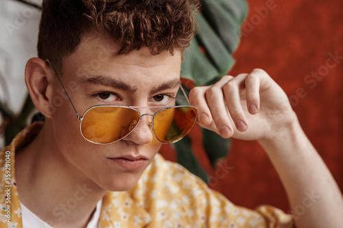 Canvastavla Fashionable young handsome man wearing trendy yellow aviator sunglasses