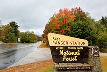 The White Mountain National Forest Saco Ranger Station Sign At The Entrance Of Kancamagus Highway With Fall Foliage In The Background.