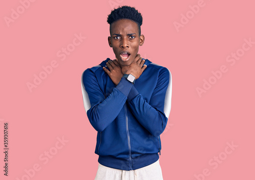 Young african american man wearing sportswear shouting suffocate because painful strangle Canvas Print