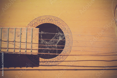 Old dusty guitar element with torn strings and cobwebs. Toned Wallpaper Mural