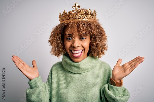 Young african american woman wearing golden crown of queen over isolated white background celebrating crazy and amazed for success with arms raised and open eyes screaming excited Fototapete