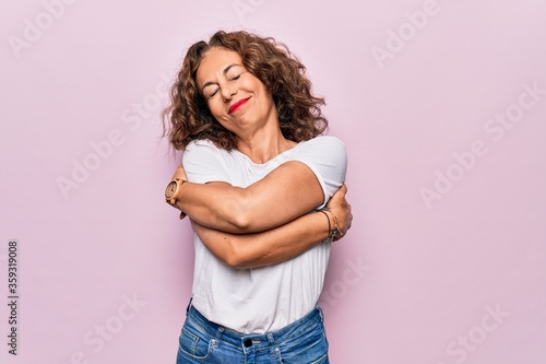 Cuadros en Lienzo Middle age beautiful woman wearing casual t-shirt standing over isolated pink background hugging oneself happy and positive, smiling confident