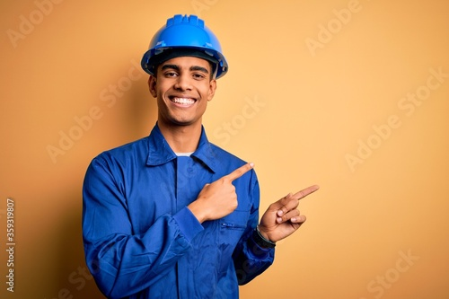 Fotografija Young handsome african american worker man wearing blue uniform and security helmet smiling and looking at the camera pointing with two hands and fingers to the side