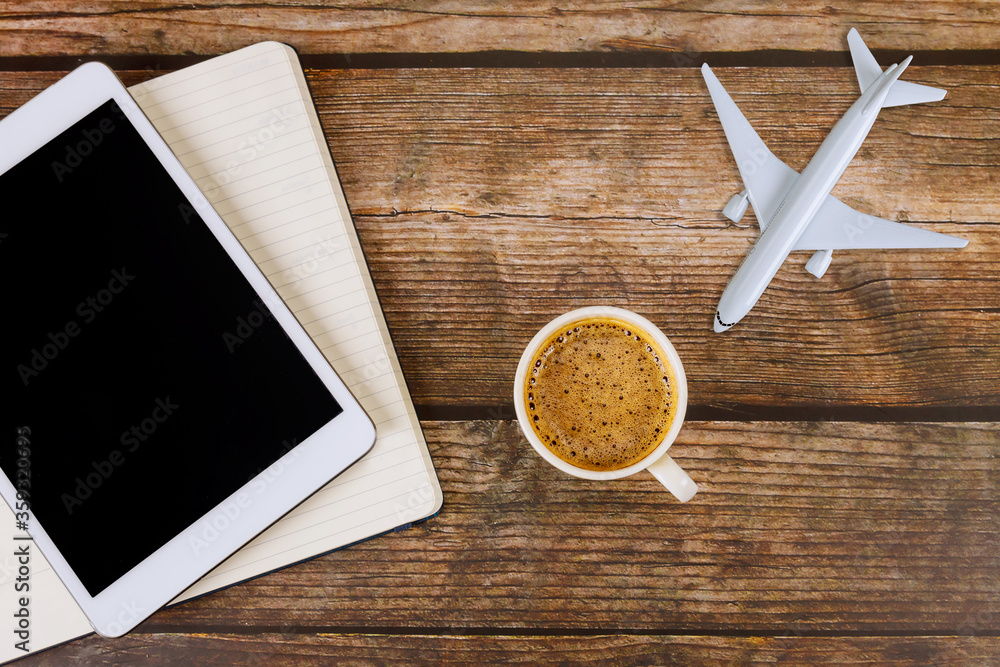 Fototapeta Summer for traveling concept on wooden table background travel concept with using digital tablet airplane model plane with blank paper notes, coffee cup