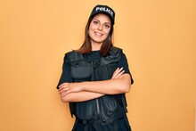 Young Beautiful Brunette Policewoman Wearing Police Uniform Bulletproof And Cap Happy Face Smiling With Crossed Arms Looking At The Camera. Positive Person.