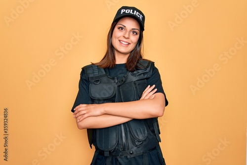 Fototapeta Young beautiful brunette policewoman wearing police uniform bulletproof and cap happy face smiling with crossed arms looking at the camera