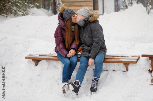 Fototapeta Young guy and a girl are kissing in a winter park. obraz na płótnie