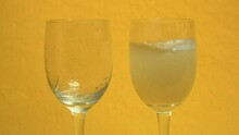 Filling Two Glasses (with A Rose Engraving) With Champagne Poured From A Bottle, On An Orange Background And With A Slight Zoom In