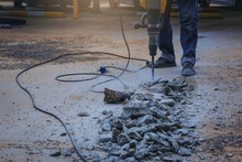 Worker Drilling Cement Concrete With Jackhammer Machine At Outdoor Construction Site