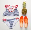 Leinwandbild Motiv Swimsuit with shoes and pineapple on white background