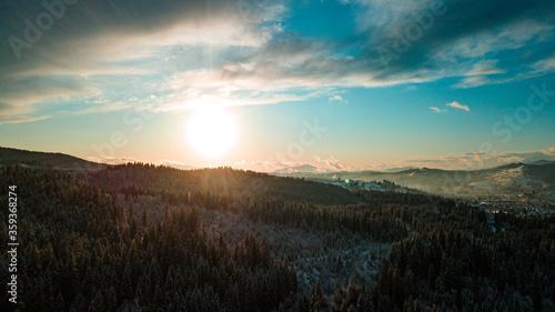 Carpathian mountains winter. Snow coniferous forest at sunset.