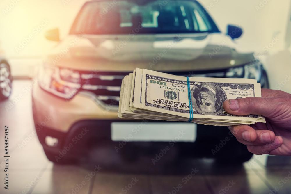 Fototapeta dealer make agreement to buy a new car, man holding dollar