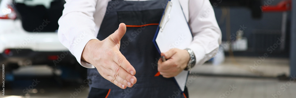 Fototapeta Close-up of professional car mechanic offer to shake hands with customer. Male worker holding checklist paper. Automobile service station and restoration workshop concept