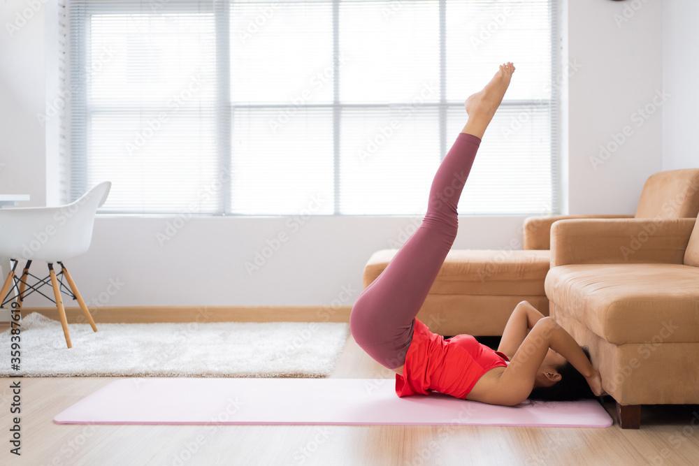 Fototapeta Asian woman Exercise at home. She uses a sofa. Abdominal exercises