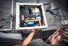 Man Installing Additional Batteries In His Camper Van