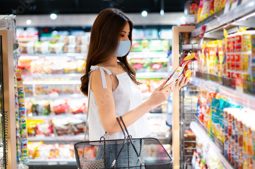 Young Asian woman with protective face mask with shopping cart basket in supermarket inside department store Tableau sur Toile
