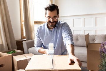 Smiling man wearing glasses packing cardboard box with adhesive tape, using dispenser, happy excited young male preparing to relocation, moving day and relocating delivery service concept