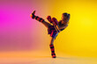 canvas print picture - Little caucasian girl, kick boxer on gradient background in neon light, active and expressive. Concept of motion, action, motivation, childhood. Training winner, emotional. Sales, ad, copyspace.