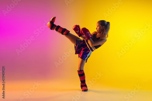 Little caucasian girl, kick boxer on gradient background in neon light, active and expressive Canvas Print