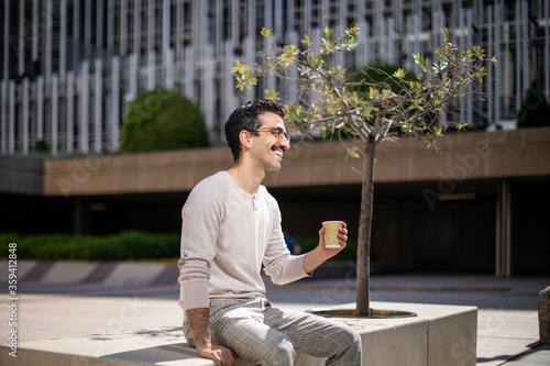 Joven trabajador feliz tomando café durante el descanso en la oficina Canvas Print