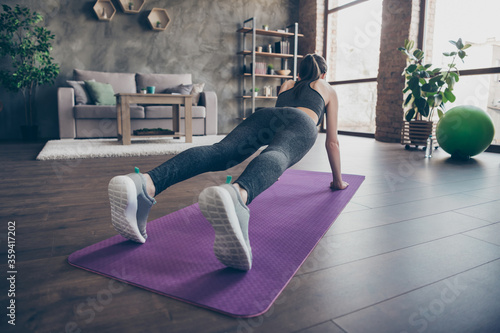 Full length back rear spine view photo of athlete beautiful girl doing push- ups aerobics plank practice effort physical exercise on mat wear panties in house indoors