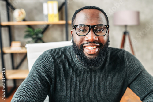Obraz Webcam shot of African-American young guy in glasses, he looks into camera and smiles. Video screen, video chat, online call - fototapety do salonu