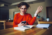 Angry Attractive Female Feeling Disappointed Receiving Bill From Banking Service Checking Email Box In Smartphone Connected To Wireless Internet, Emotional Hipster Girl Upset About Failure Of Payment