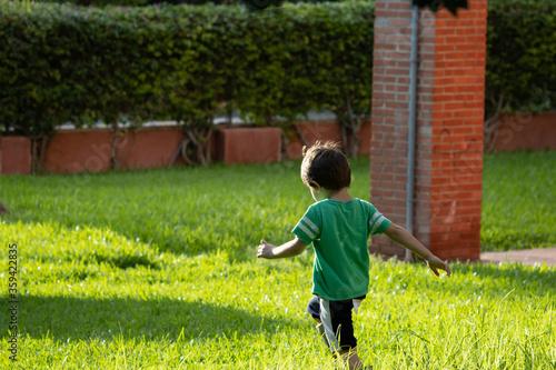 niño alegre camiseta verde jugando jardín soleado Canvas Print