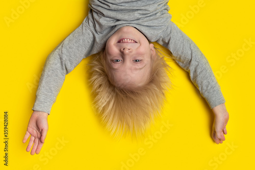 Photo Funny boy with blond hair hanging upside down