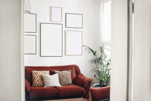 Blank Picture Frames Mockups On White Wall. White Living Room Design. View Of Modern Boho, Scandi Style Interior With Sofa, Cushions, Potted Palm Plant Through Open White Door. Home Staging Concept.