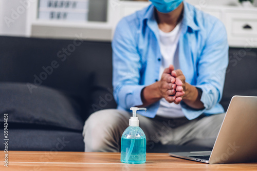 Young man washing hands with alcohol gel in quarantine for coronavirus wearing protective mask with social distancing and using laptop computer working at home.work from home and covid19 concept