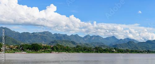Panorama sur les berges du fleuve Mékong entourée de montagnes avec plusieurs bateaux amarrés au Laos. #359434409
