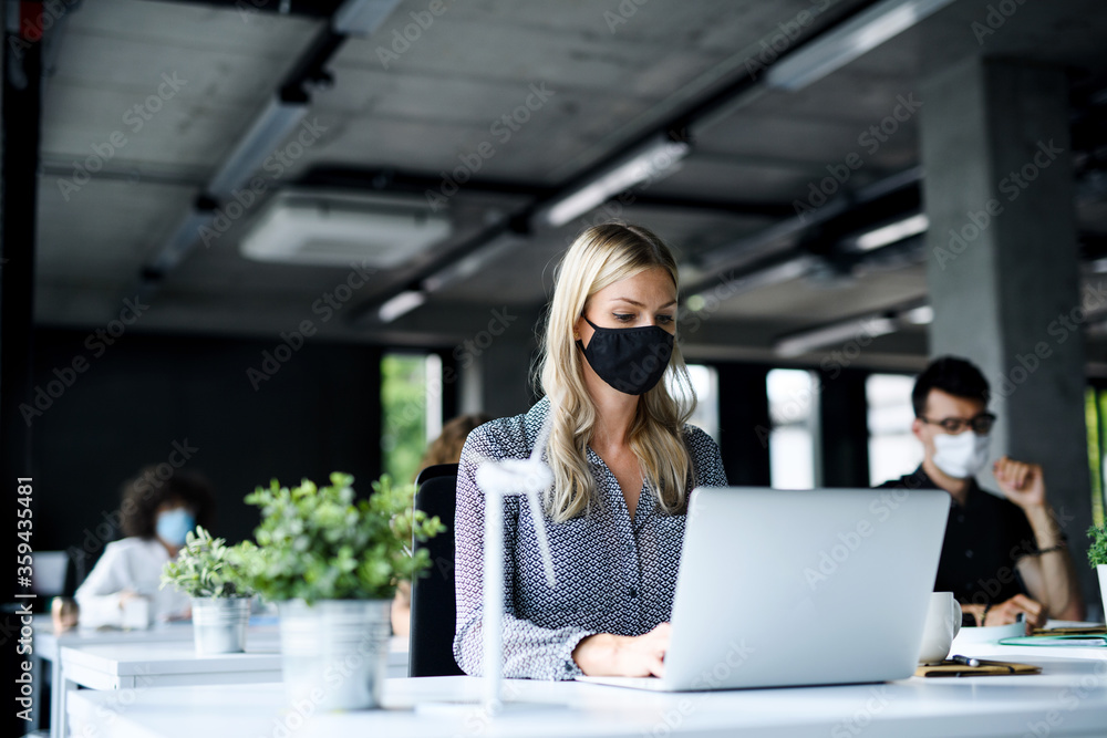 Fototapeta Young people with face masks back at work or school in office after lockdown.