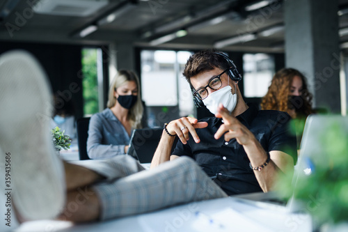 Fotografie, Obraz Young man with face mask back at work or school in office after lockdown, having fun