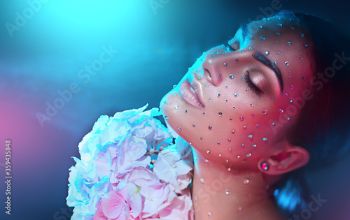 Beauty fashion Woman face decorated with gem stones, crystals, diamonds Closeup Art Portrait with Hydrangea flower. Model girl, holiday Glamour shiny make up with gems, jewellery, jewelry, accessories