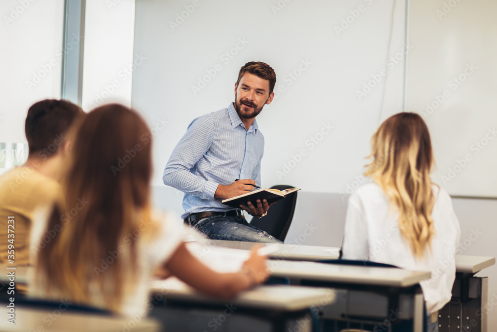 Fototapeta Smiling teacher standing in front of students and showing something on white board in classroom