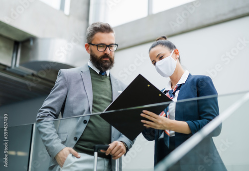 Fototapeta Flight attendant talking to unrecognizable businessman on airport, wearing face masks. obraz