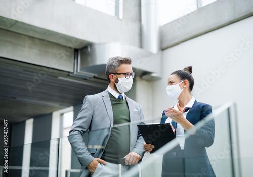Flight attendant talking to businessman on airport, wearing face masks Wallpaper Mural