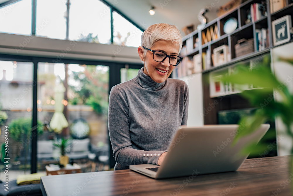 Fototapeta Portrait of a cheerful mature businesswoman working on laptop at home office.