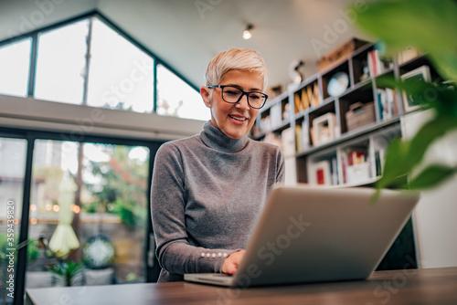 Canvastavla Portrait of a beautiful modern senior woman using laptop, low angle image