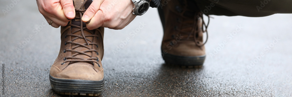 Fototapeta Close-up view of male hands sitting down outside on street and tying shoelaces on sneakers. Person lacing up stylish shoes. Sport walking and running concept