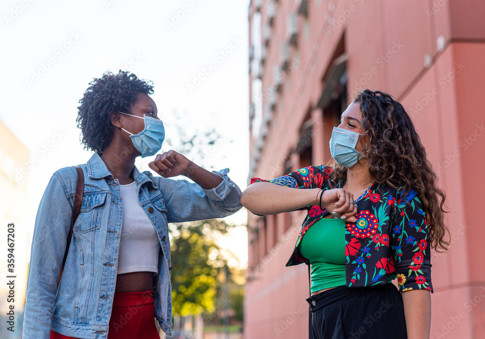 Fototapeta Young and friendly african girl and caucasian girl keeping social distance, greeting each other by bumping elbows instead of hugs, kisses or handshaking, wearing mask for prevent coronavirus infection