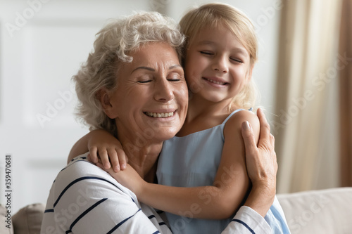 Close up view loving grandmother cuddle snuggle to small granddaughter people cl Canvas