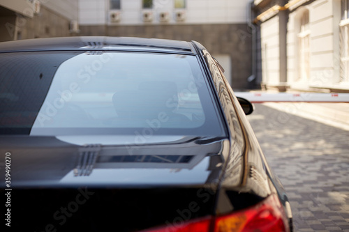 Back window of black car parked on the street in summer sunny day, rear view. Mock-up for sticker or decals © Alexey