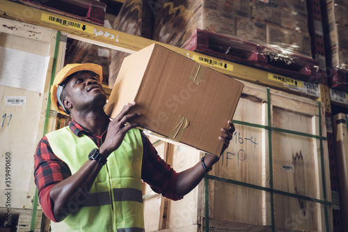 African American black man carry heavy box on shoulder in warehouse production Fototapet