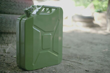 Canister Of Gasoline. Green Metal Military Style Jerrycan With Free Space For Text On Blurred Background