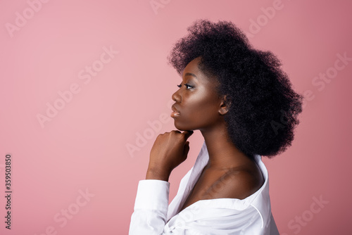 Elegant beautiful African American woman wearing classic white shirt,  posing in studio, on pink background Canvas Print