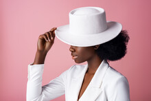 Elegant Beautiful African American Woman Wearing Classic White Blazer, Hiding Eyes By Stylish Hat, Posing In Studio, On Pink Background. Close Up Profile Portrait.