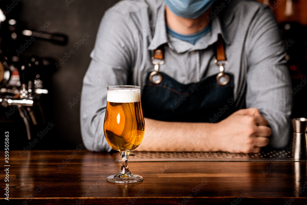 Fototapeta Bartender in protective mask leans on bar counter on which stands glass of light beer with foam