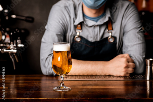 Fototapeta Bartender in protective mask leans on bar counter on which stands glass of light beer with foam obraz